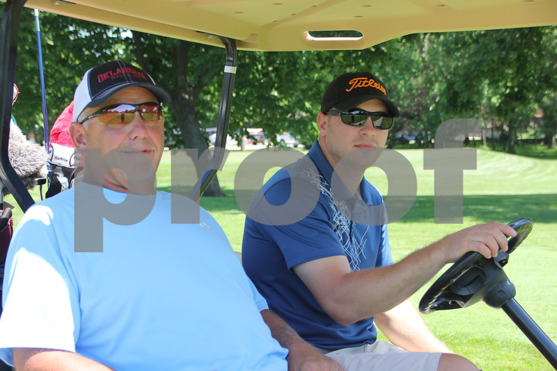 Tommy and Bobby Thompson stop for a picture on their way to one of 18 holes on the golf course. They took part in the Swing for A Cure event held on Friday, June 19, 2015 to raise money for diabetes. The event took place at the Fort Dodge Country Club.