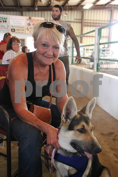 Rose Mallison and her dog Lily, who is being given socialization training, were cheering on some of their family members who were competing in the Barnyard Olympics at the Webster County Fair on Friday, July 10, 2015.