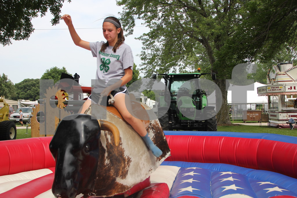 Sidney Messerly takes a ride on the mechanical bull at the Webster County Fair on Friday, July 10, 2015. The mechanical bull was just one of  several options for fun  that kids had to choose from.
