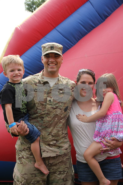 Seen left to right are : Parker, Travis (in uniform), Kimberly, and Kaylee Blunck having fun as a family, taking in all the sights and attractions of the Webster County Fair on Friday, July 10, 2015. Here their kids  have fun on the giant inflatable  slide.