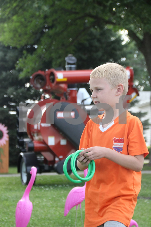 Cian O'Halloran plays a ring toss game at the Webster County Fair on Friday, July 10, 2015.