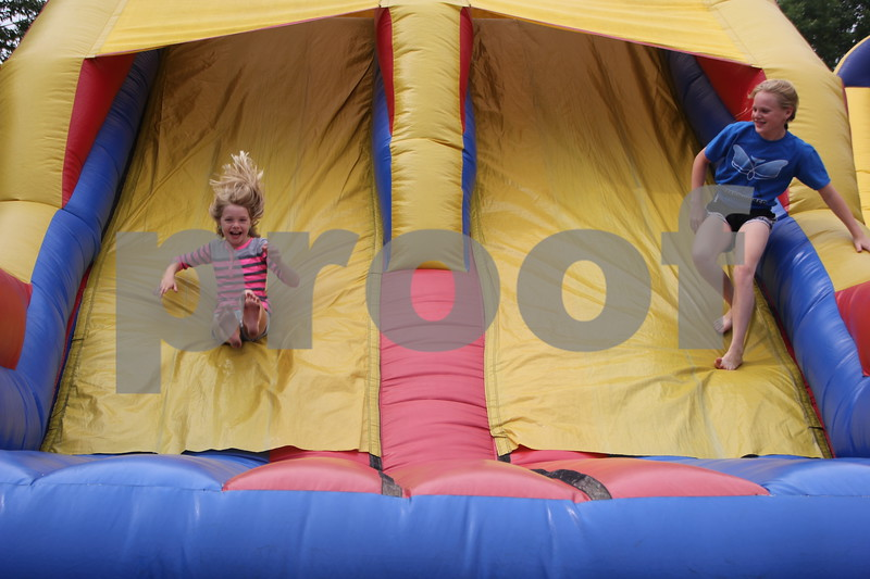 (Left to right )Morgan Bodholdt and Rylie Steinkamp enjoy the slide portion of the inflatable climbing wall at the Webster County Fair on Friday, July 10, 2015.