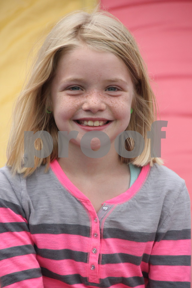 Morgan Bodholdt takes a breather from her fun on the inflatables, to get a picture taken at the Webster County Fair on Friday, July 10, 2015.
