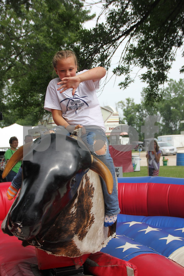 Teighan Osborne tries her luck on the mechanical bull at the Webster County Fair on Friday, July 10, 2015. The bull was one of several attractions for kids to do for fun.