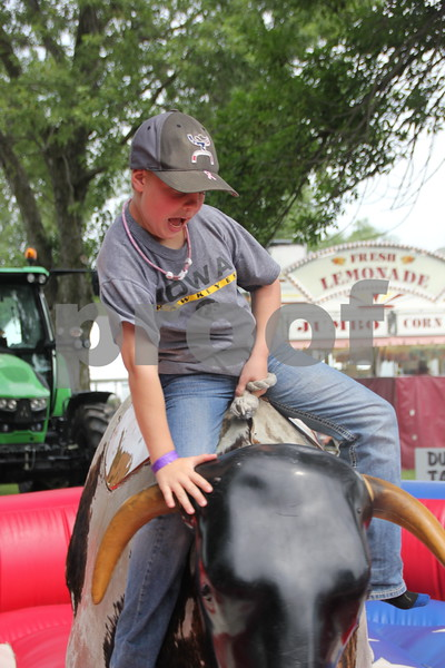 Dusty Pate tries to hang on tight as he takes his turn on the  mechanical bull at the Webster County Fair on Friday, July 10, 2015.