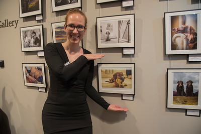Monika Madi next to her award winning photograph for Puppies category