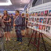 Attendees of the 2015 Women In Business Awards stand next to a roster of high school photos of each of this years winners before the dinner and ceremony.