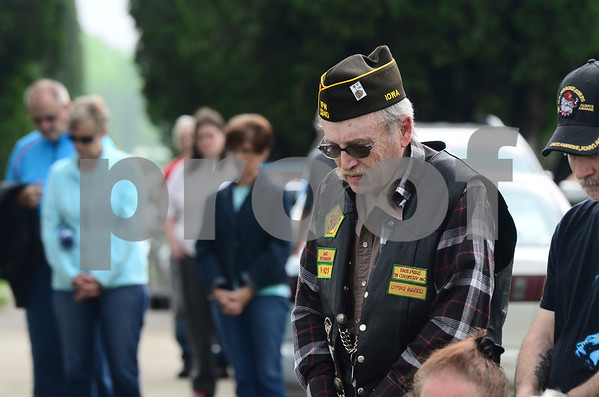 -Messenger photo by Jesse Major<br /> <br /> Don Kelly, a Vietnam veteran, bows his head during a moment of silence for soldiers who died at war during the Memorial Day service in Eagle Grove.