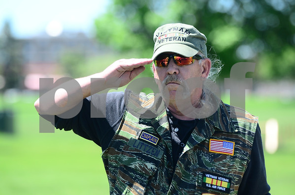 -Messenger photo by Jesse Major<br /> <br /> Michael Litzen salutes as the Star Spangled Banner is played during the ceremonial dedication of the Vietnam Vetrans Memorial Bench outside the Fort Musuem Monday.