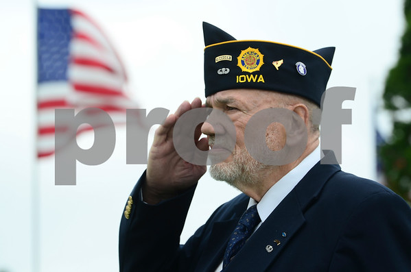 -Messenger photo by Jesse Major<br /> <br /> An American flag waves behind Larry Ivers, commander of American Legion Post 304 in Eagle Grove, as he salutes during the national anthem.