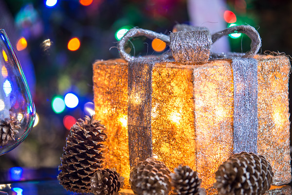 lit Christmas present under a Christmas tree with defocused lights
