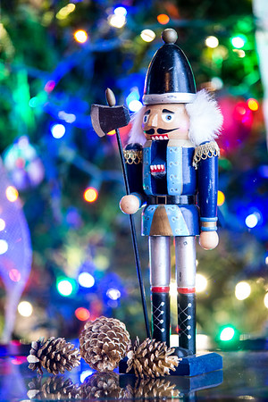 Soldier nutcracker statue standing in front of decorated Christmas tree