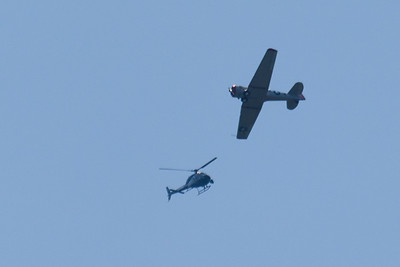 "Local news helicopter and the ""air boss"" flying in an AT-6 ""Texan""."