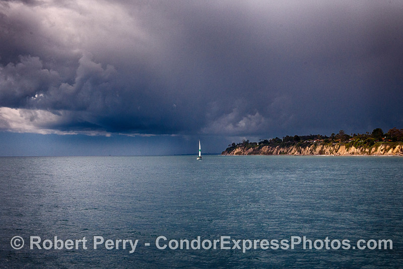 "The sailboat ""Sunset Kid"" rounds Santa Barbara Point as a rain squall makes its approach."