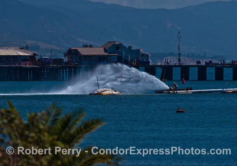 "The harbor dredge ""La Encina"" pumps water from its effluent pipe with Stern's Wharf in the background."