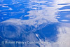 Image 3 of 3:  Tropical skies seen reflected on a mirror-glass sea surface.