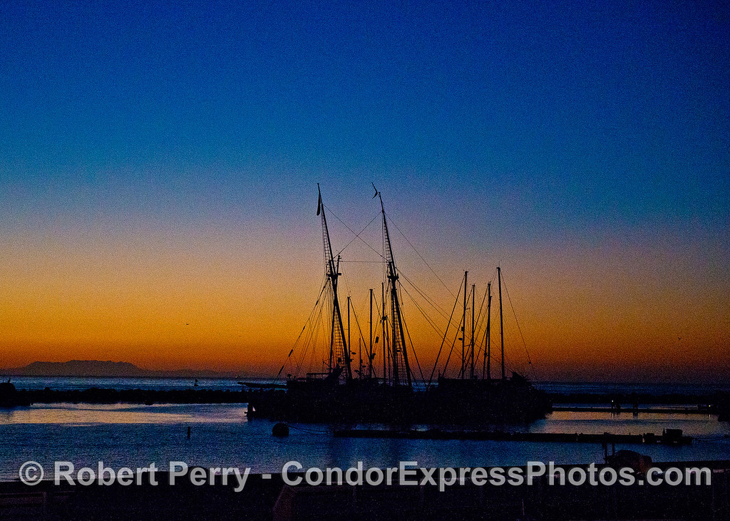 "Sunrise through the masts and rigging of various sail boats in Santa Barbara including the tall ship ""Spirit of Dana Point.""   Boney Ridge in the Santa Monica Mountains is seen in the distance."
