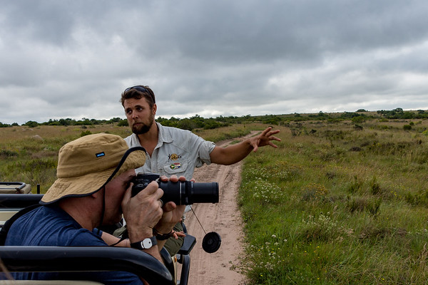 A picture of a South African meadow with a guide gesturing as a photographer takes a picture.