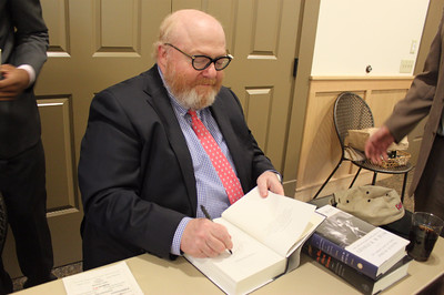 Richard Norton Smith autographs a copy of his book On His Own Terms A Life of Nelson Rockefeller