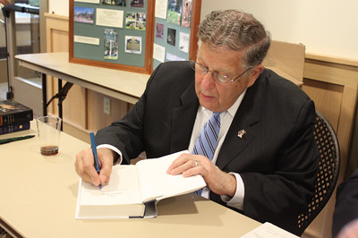 Gov  John Sununu autographs a copy of his book The Quiet Man, The Indispensable Presidency of George H W  Bush