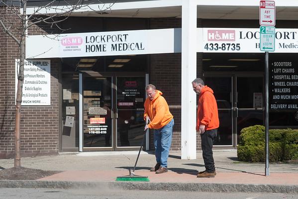 JOED VIERA/STAFF PHOTOGRAPHER-Lockport, NY-Crews clean up the sidewalk on Mains Street.
