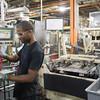 JOED VIERA/STAFF PHOTOGRAPHER-Lockport, NY-Machine operator Charles Burton assembles radiators at the GM Plant.