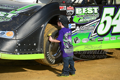 A young race fan looks under Matt Westfall's car