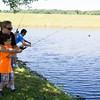 Melissa Massari of Youth Advocate Program assists six-year-old John during TEAM Newburgh's seventh annual fishing trip to Lake Washington on Thursday, July 23, 2015. Hudson Valley Press/CHUCK STEWART, JR.