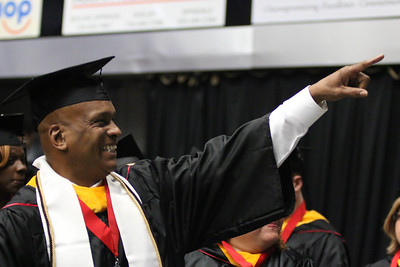A graduating student points to his friends/family. Photo by Megan Hartman