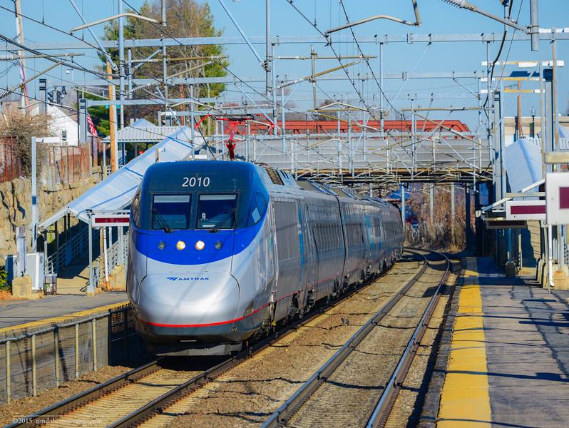 Acela 2163 zips through Hyde Park Station in Boston.