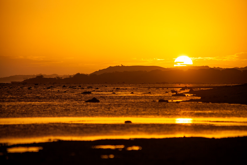 """The sun sets over mainland Fiji as we watch from the beach near our bungalow, aptly placed on the area referred to as the """"Sunset Strip."""""""