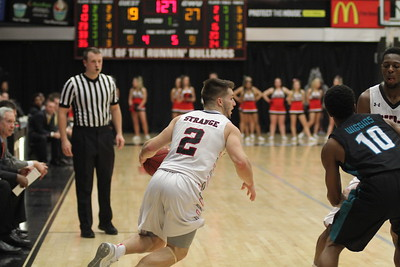 2, Tyler Strange, handles the basketball.