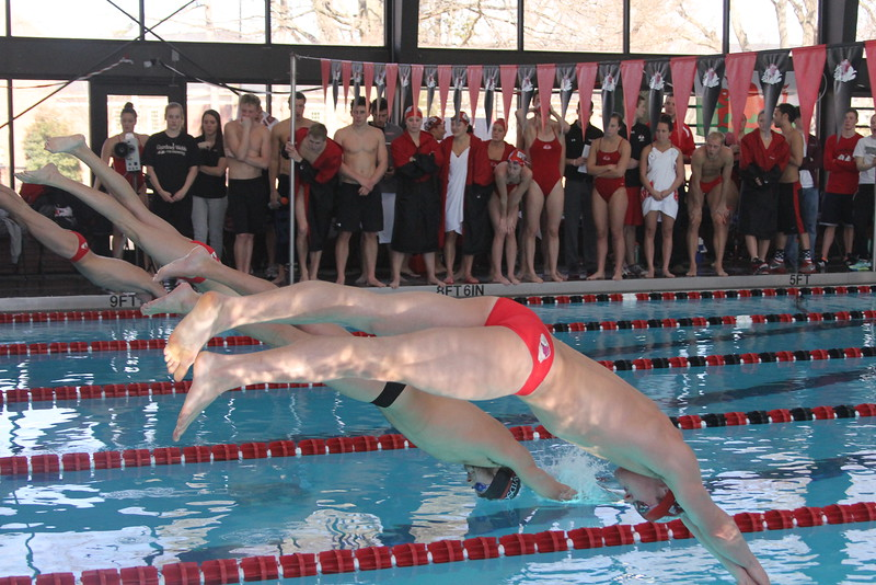 Swimmers explode off the starting block.