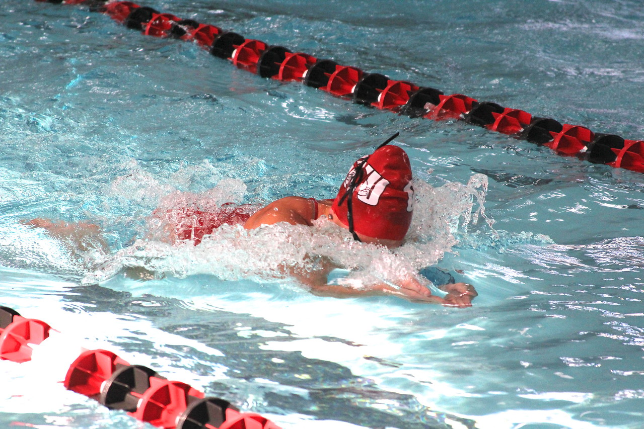 Swimmers compete in the breaststroke.