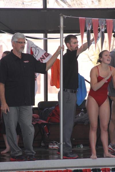GWU swim coaches cheer on their team.