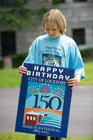 JOED VIERA/STAFF PHOTOGRAPHER-Lockport, NY-Jessica Booth 10 puts up a Sesquicentenial sign on Pine Street.