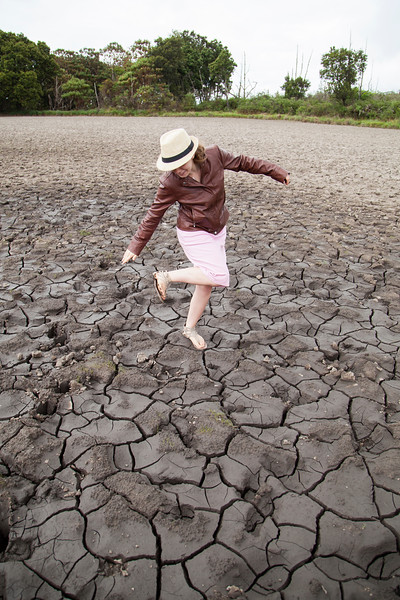 Ashley cleans the mud off her feet in the middle of a dried lake bed in Nyika National Park.