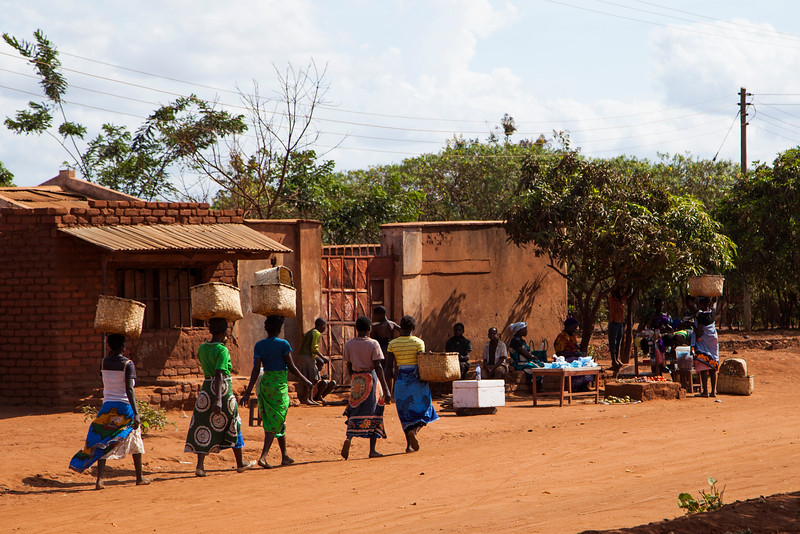 Ladies carry their goods in large baskets on their heads, wandering down a dirt road past the church where we had service Saturday morning.