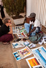 Tracy checks out the wares sold by Manyana, a local artist who makes his living pedling paintings on the streets of Mzuzu.
