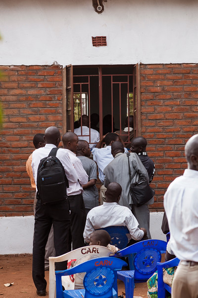 Men watch through the windows during Saturday evening's service at the dedication meetings at Bro. Raphael's church in Lilongwe.
