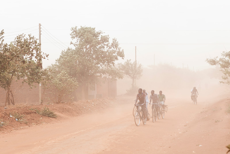 Wind blasts passersby with sand and dirt on a dusty Lilongwe street.
