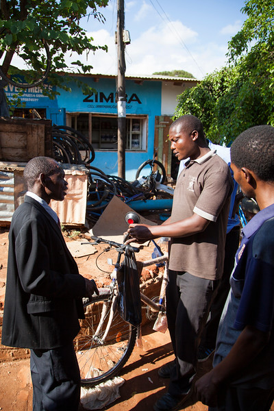 A mechanic accepts the job of readying this new bicycle for use by a local missionary brother.