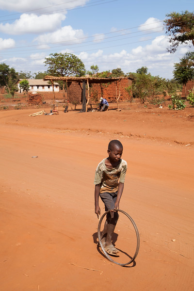A young boy pushes a bicycle wheel down the road, with a local repairman at work in his shop in the background.