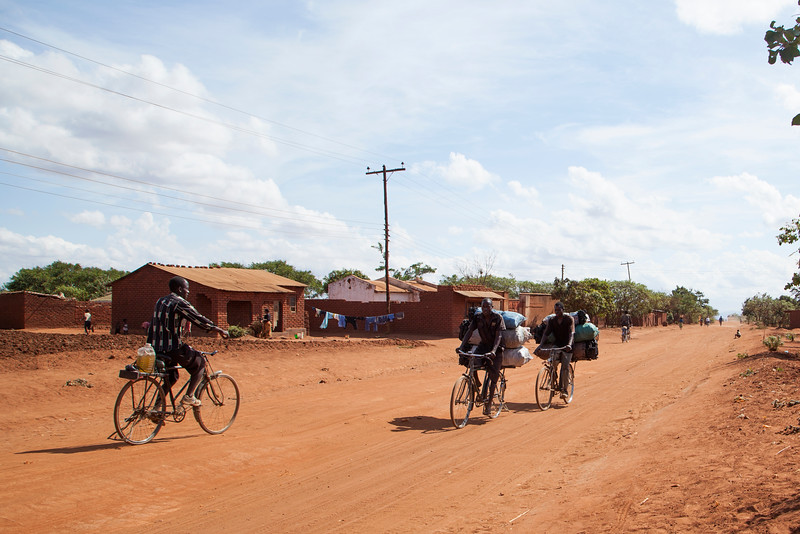 Men carry rather large loads of charcoal on rickety bicycles, headed for a market a few miles down this dirt road.