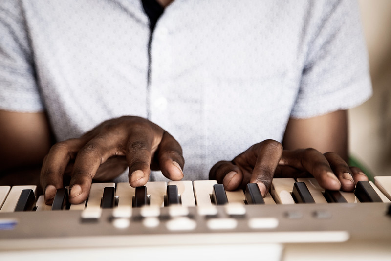 Bro. Precious plays the piano during a singing fellowship in a local pastor's garage.