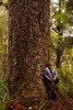 Kelsey leans against a Kauri as he stares skyward into its branches, supporting all manner of life high above the forest floor.