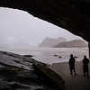 Kelsey and Tracy wait out a heavy rain squall in a small cave at Wharariki Beach.