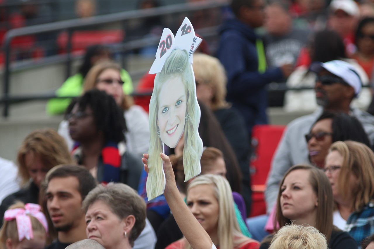 Fan's hold up a giant cut out head of cheerleader Kaylan Myers.