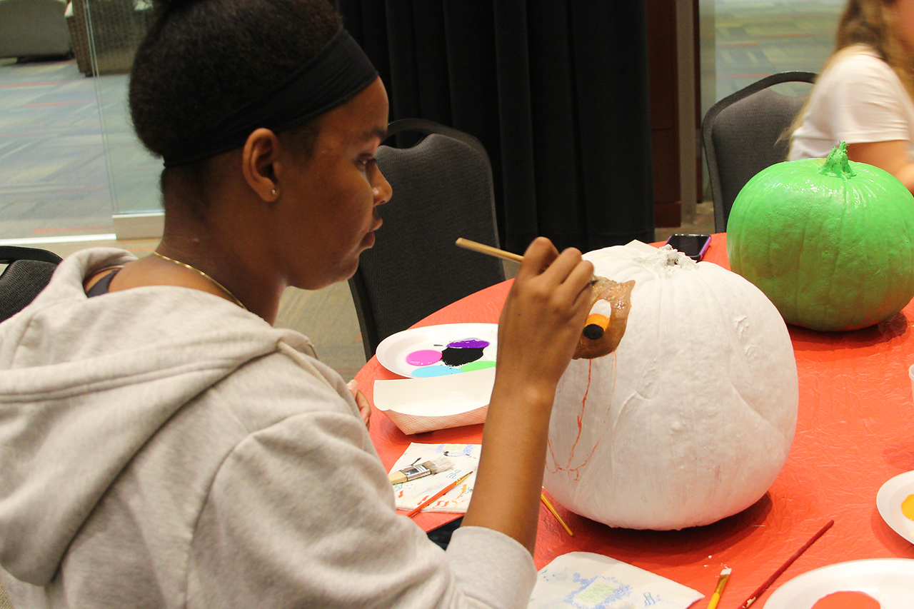 Students gathered in the Tucker Center to paint pumpkins for Halloween.