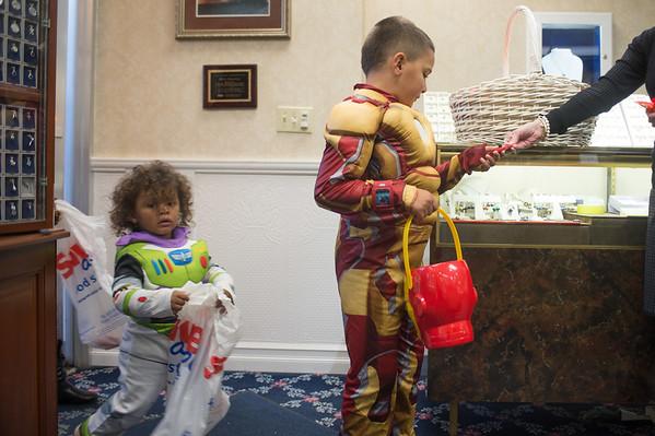 JOED VIERA/STAFF Lockport, NY-Zackary Moss Pagan 7 (Iron Man) and Joseph Marshall Herring 2 (Buzz Lightyear) grab snacks at Mills Jewelers during Downtown Trick or Treating.